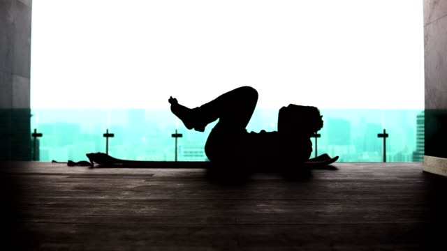 silhouette of a man doing abdominal exercises on the background of the metropolis - man city exercise abs video stock e b–roll