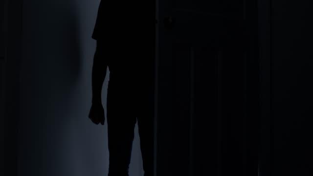 vídeos y material grabado en eventos de stock de silueta de un hombre entrando en una habitación oscura, el puño apretado. - violencia doméstica