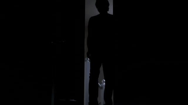 silhouette von einem mann, die eingabe einer dunklen zimmer. - mann tür heimlich stock-videos und b-roll-filmmaterial