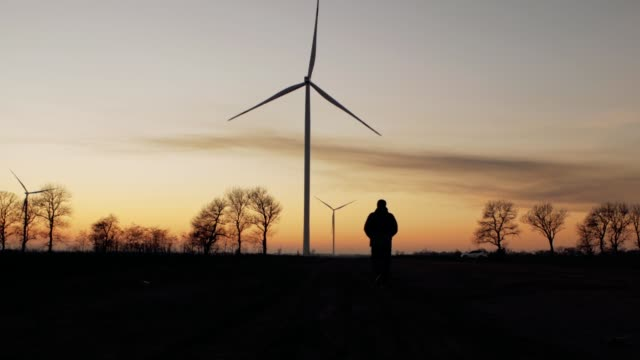 silhouette of a man goes to sunset in the direction of wind turbines - энергия ветра стоковые видео и кадры b-roll