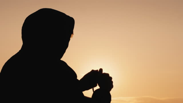 Silhouette of a man in the hood, sifting through the rosary at sunset video