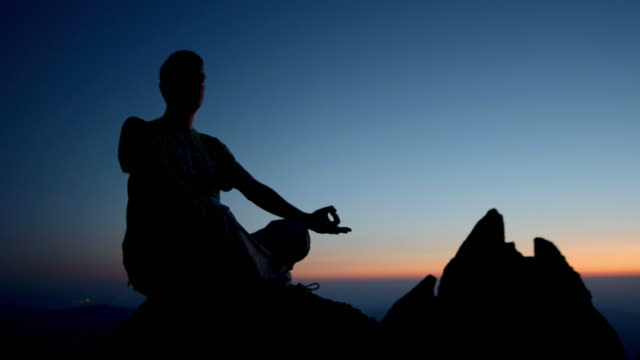 HD DOLLY: Silhouette Of A Man Meditating HD1080p: DOLLY shot of a silhouette of a man meditating on a cliff at sunset. zen like stock videos & royalty-free footage