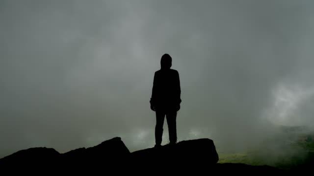 vídeos de stock e filmes b-roll de silhouette of a man on a background of gray fog. - capuz