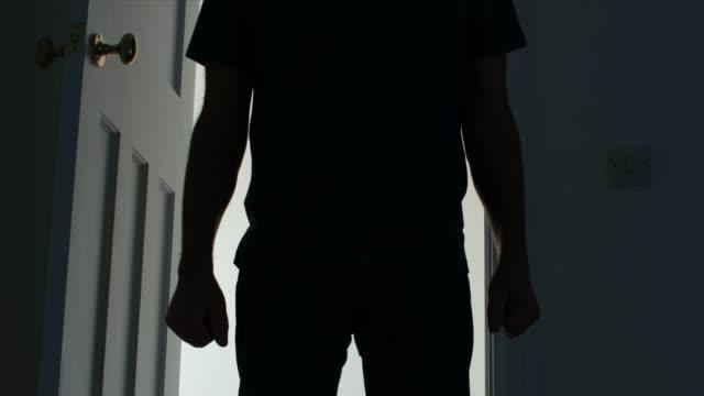 vídeos y material grabado en eventos de stock de silueta de un hombre que se abre una puerta y entrar en una sala oscura, sin editar. - violencia doméstica