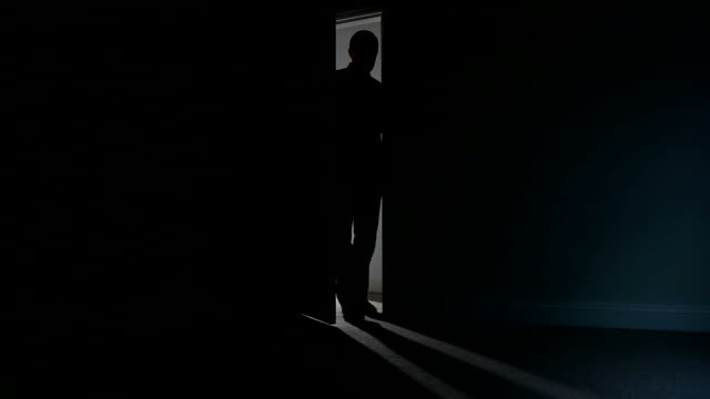 Silhouette of a man opening a door to dark room. video