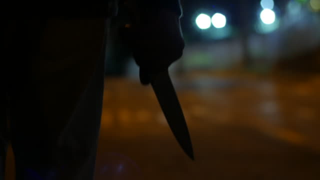 Silhouette of a man walking at night holding a big knife