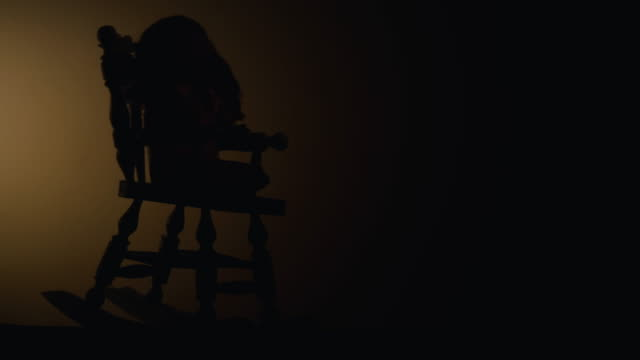 Silhouette of a rocking chair and a doll on it. Horrible scene.