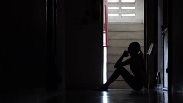 silhouette of a sad young girl sitting in the dark leaning against the wall in old condo, domestic violence, family problems, stress, violence, the concept of depression and suicide. - samotność filmów i materiałów b-roll