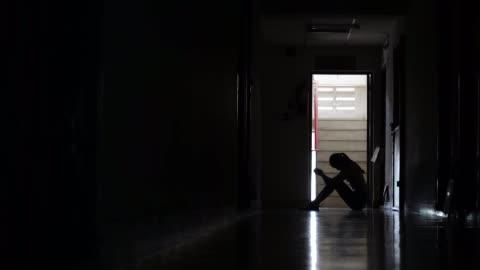 karanlık eski daire, ev içi şiddet, aile sorunları, stres, şiddet, depresyon ve intihar kavramı duvar karşı eğilmek oturan üzücü bir genç kız silüeti. - kızlar stok videoları ve detay görüntü çekimi