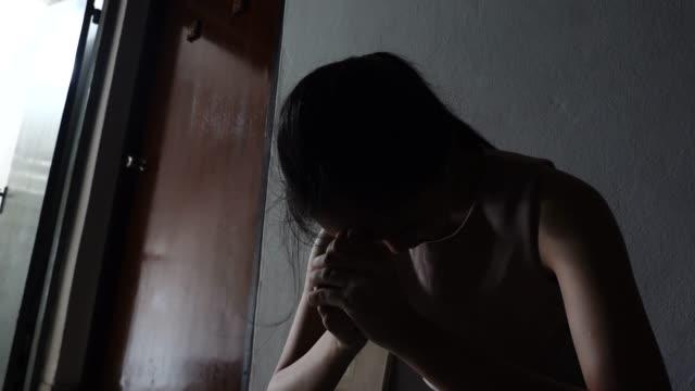 stockvideo's en b-roll-footage met silhouet van een trieste jonge meisje zit in het donker leunend tegen de muur in de oude condo, huiselijk geweld, familie problemen, stress, geweld, het concept van depressie en zelfmoord. - overstuur