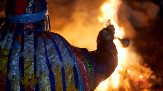 vidéos et rushes de silhouette d'un chaman s'asseyant près du feu. - charmeur