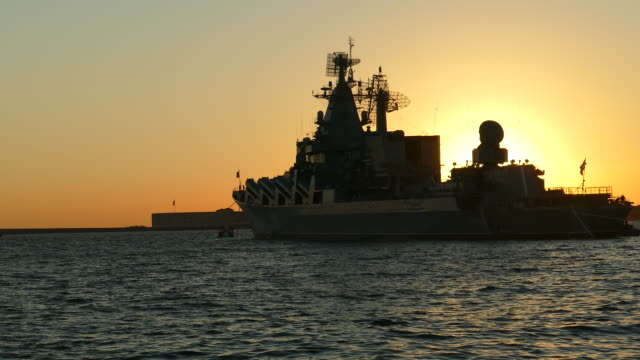 silhouette of a warship and the sun at sunset - caravan stock videos & royalty-free footage