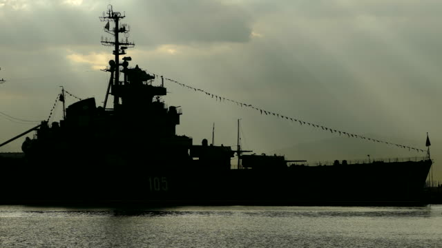 Silhouette of a warship of the Cold War at dawn