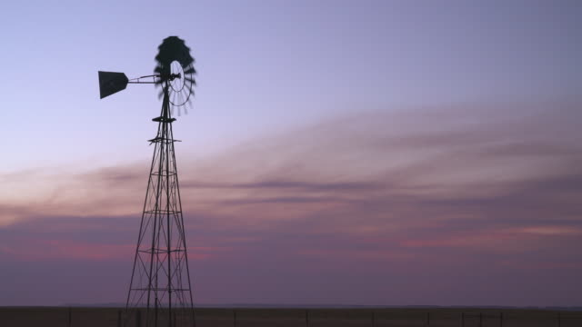 Silhouette of a windmill pumping water Silhouette of a windmill pumping water for cattle at Colorado prairie prairie stock videos & royalty-free footage