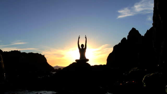 Silhouette of a woman meditating at sunset video