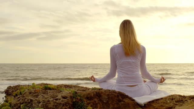 실루엣 있는 여자 명상하기 비치에서 at 썬라이즈 - wellness 스톡 비디오 및 b-롤 화면