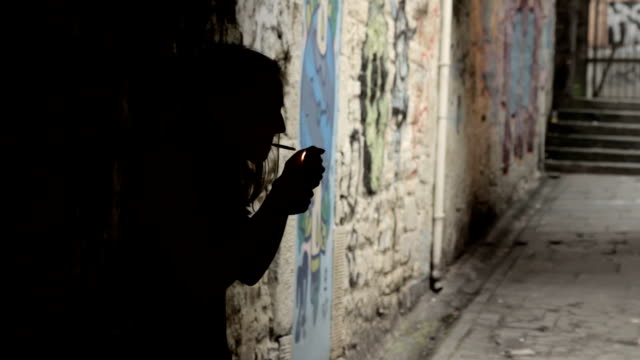 Silhouette of a woman smoking in an alleyway