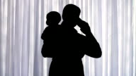 istock Silhouette of a woman standing in front of a window, carrying a baby and talking on a cellphone 1216884029