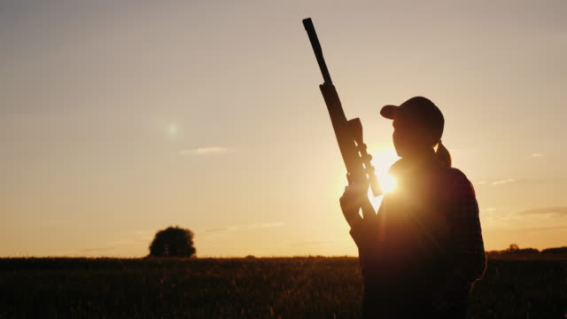 silhouette of a woman with a sniper rifle. standing in the rays of the setting sun - cacciatore video stock e b–roll