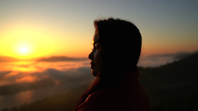 Silhouette of a women hiker in the mountains with a sea of mist in the valley in the hours of sunset.