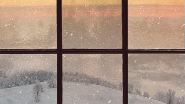 vídeos de stock e filmes b-roll de silhouette of a wooden window overlooking the evening winter forest. beautiful winter landscape with falling snow - living room background
