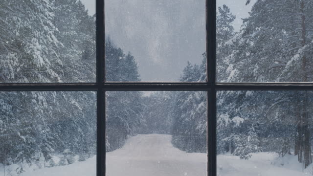 Video Silhouette of a wooden window overlooking the winter forest. Beautiful winter landscape with falling snow.