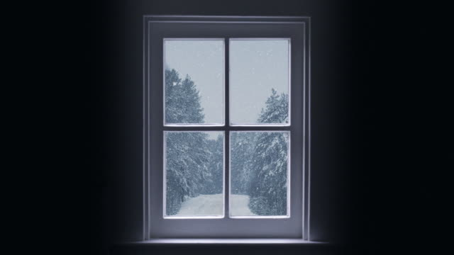 Silhouette of a wooden window overlooking the winter forest. Beautiful winter landscape with falling snow.