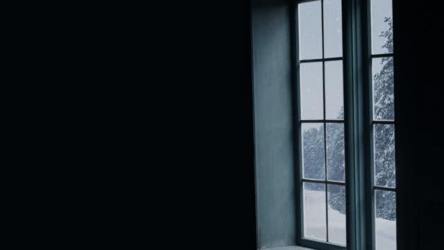 silhouette eines holzfensters mit blick auf den winterwald. schöne winterlandschaft mit fallendem schnee. - blockhütte stock-videos und b-roll-filmmaterial