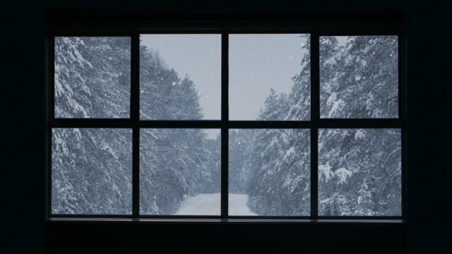 vídeos de stock e filmes b-roll de silhouette of a wooden window overlooking the winter forest. beautiful winter landscape with falling snow. - background christmas snow