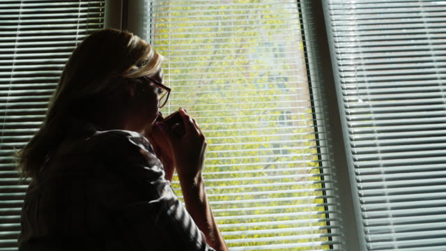 Silhouette of a young woman by the window. He looks at the street through the blinds, drinks coffee from a cup. Looks forward video