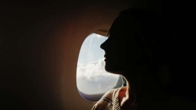 silhouette of a young woman flying in an airplane. Sitting near the window, where you can see the sky and clouds in motion video