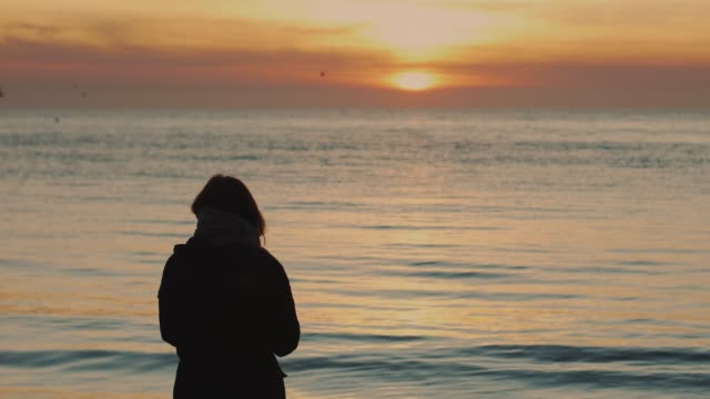 Silhouette of a young woman on a background of the sea. Sunset or sunrise on winter day in Odessa
