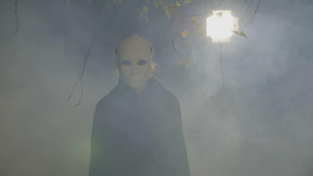 Silhouette of a zombie with a white mask on his face walking to the camera in a forest at midnight halloween video