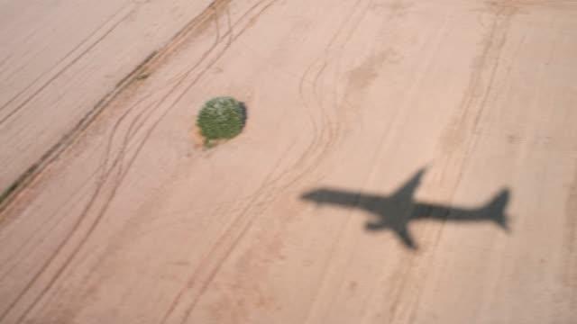 sylwetka samolotu latającego nad polami. cień samolotu ląduje nad złotymi polami pszenicy. lot samolotem - lądować filmów i materiałów b-roll