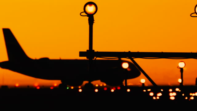 Silhouette of airplanes at the airport at sunny orange and purple sunset. Plane taxiing on the runway preparing for journey. Runway end identification lights and strobe glowing.