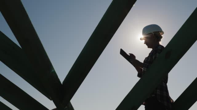 vídeos y material grabado en eventos de stock de silueta de un ingeniero, trabajos entre las vigas del techo, utiliza una tableta. control técnico en construcción - arquitecto