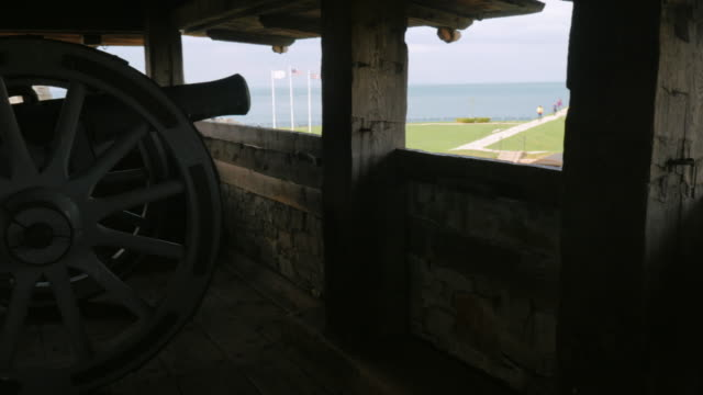 Silhouette of an old cannon at Fort Niagara. Its trunk looks at trees. Side view video
