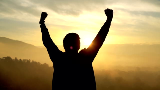 silhouette of arms raised man in sunrise - in cima video stock e b–roll