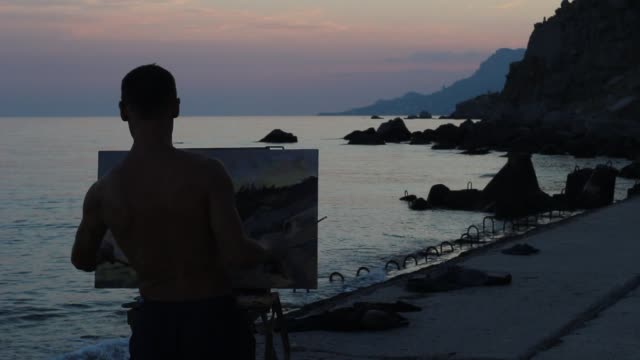 silhouette of artist who paints beautiful sunset on the rocky coast - painter stock videos and b-roll footage