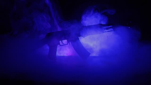 Silhouette of assault rifle on toned foggy background. War or antiterrorism concept. Russian military weapon on table. Slider shot video