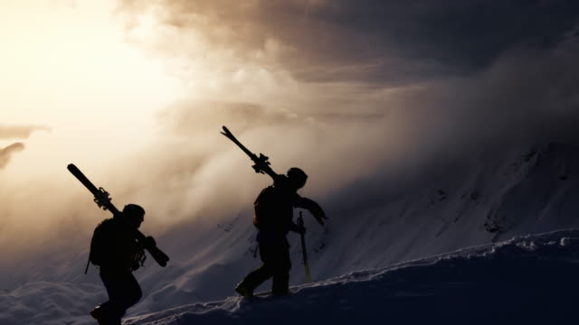 aerial silhouette of backcountry skier walking up mountain ridge - sci attrezzatura sportiva video stock e b–roll