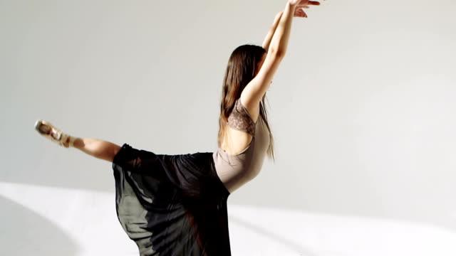 silhouette of ballerina in classical tutu in the white studio. video