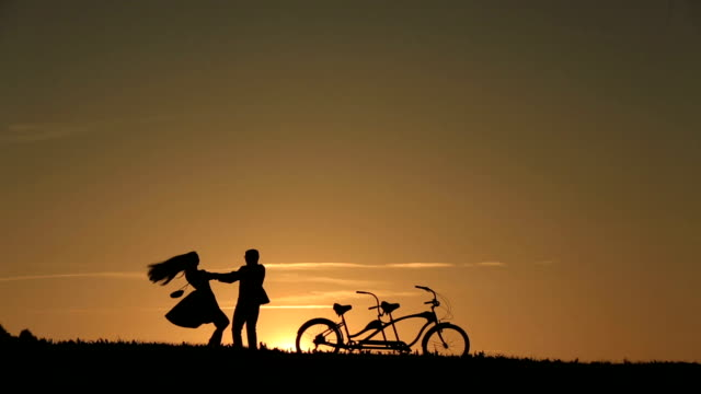 Silhouette of  Beautiful Couple With Tandem Bicycles Dancing Holding Hands Against Fabulous Sunset Backgrund Close Up