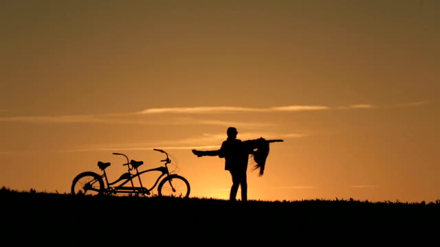 Silhouette of  Beautiful Couple With Tandem Bicycles. Man Dancing Holding her in His Arms While Sunset. Summer Nature Background with Beautiful Clouds in the Sky Close Up