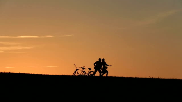 Silhouette of  Beautiful Couple With Tandem Bicycles Playing Catch  Against  Sunset On The Background Close Up