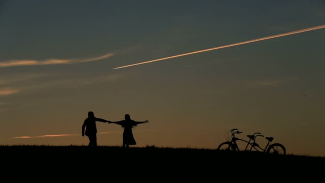 Silhouette of  Beautiful Couple With Tandem Bicycles Playing With Holding Hands Against  Sunset On The Backgrund Close Up