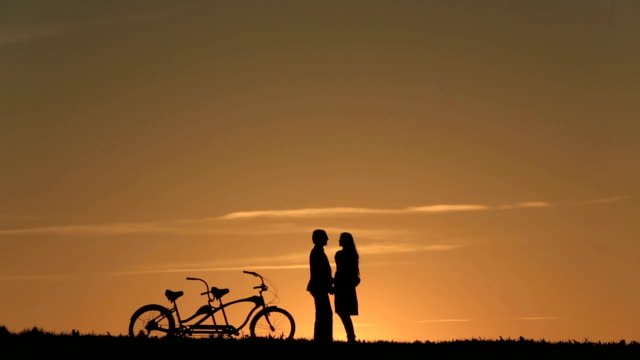 Silhouette of  Beautiful Couple With Tandem Bicycles Watching And Enjoying The Sunset Sky Close Up