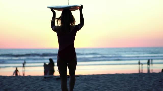 美しいサーファーの女の子のシルエットは、夕日にビーチを歩きます。スローモーション。 - ビーチファッション点の映像素材/bロール