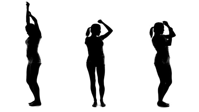 Silhouette of beautiful woman dancing and listening music
