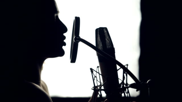 silhouette of beautiful woman is singing a song in front of a microphone in an audio recording studio on a white background. - cantante video stock e b–roll